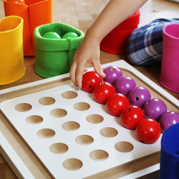 Kind legt Holzperlen auf das Perlenbrett des Junior Lege-Sets für Kinder