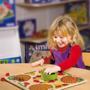 Ein Kind spielt das Gesellschaftsspiel Mecki & Co von Beleduc aus Holz für den Kindergarten