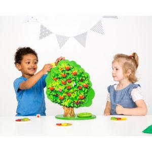 Zwei Kinder beim Spielen des Gesellschaftsspiels Apple Garden von Beleduc aus Holz für den Kindergarten