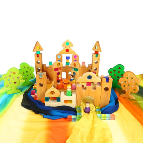 Märchenschloss gebaut aus Holzbausteinen und Glitzersteinen auf einer Landschaft aus Chiffon-Seidentüchern für Kinder im Kindergartenalter