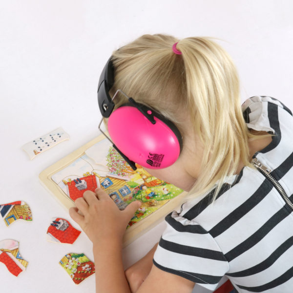 Kind mit Lärmschutz-Kopfhörer in pink arbeitet konzentriert an einem Puzzle