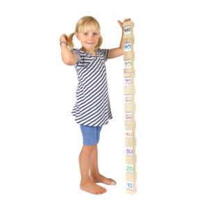 Kind misst sich mit 4/4 Bausteinen ab: alle 4 Bausteine zusammen ergeben genau 100 cm.