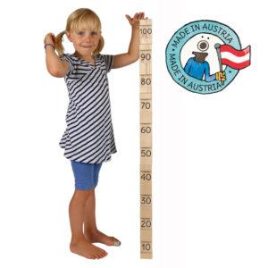 Kind misst sich mit 4/4 Bausteinen ab: alle 4 Bausteine zusammen ergeben genau 100 cm. Daneben eine Grafik mit dem Text: Made in Austria.