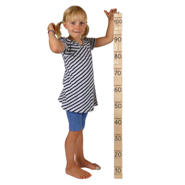 Kind misst sich mit 4/4 Bausteinen ab: alle 4 Bausteine zusammen ergeben genau 100 cm