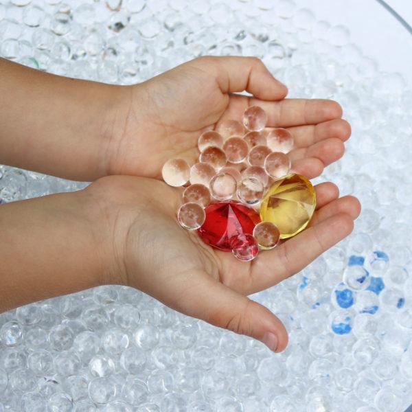 Kinderhände suchen Glasdiamanten aus einer Schüssel voller Wunderperlen