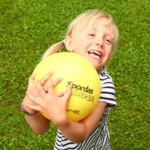 Kind fängt gelben Turnball mit beiden Händen