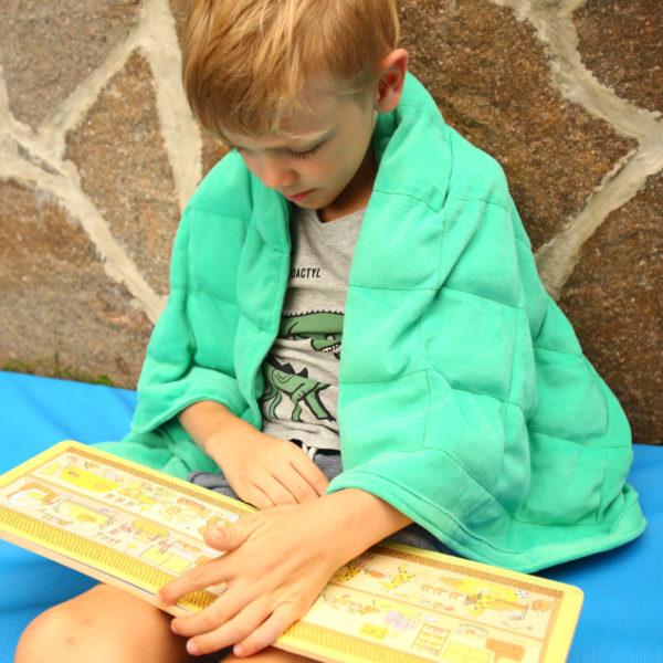 Kind liest mit Gewichtsdecke über der Schulter