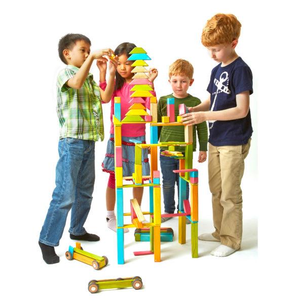 Vier Kinder bauen hohe Türme aus tegu Magnetbausteinen aus Holz