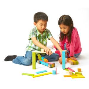 Zwei Kinder spielen mit den tegu Magnetbausteinen aus Holz