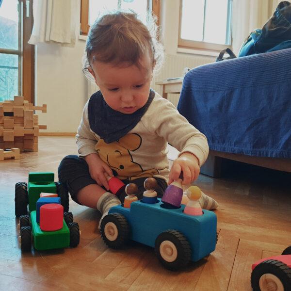 Kleinkind spielt mit Autos, Traktor und Figuren aus Holz