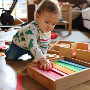 Kind spielt mit bunten Brettchen von Bauspiel