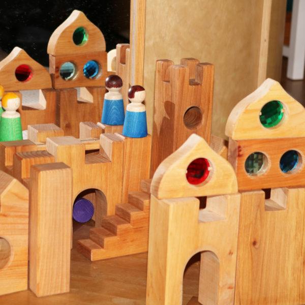 Nahaufnahme Holzbausteine für Kinder: Ritterburg mit Holzfiguren und Märchenschloss-Fenstern