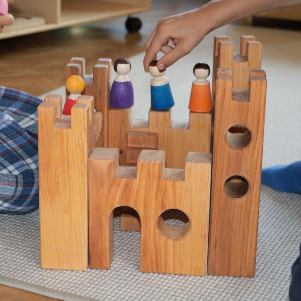 Kinder spielen mit der 10-teiligen Rittterburg aus Holz und den Holzfiguren von Bauspiel
