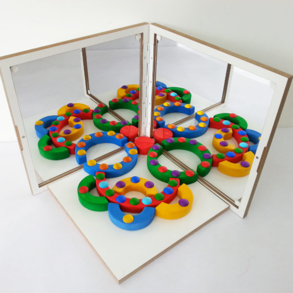Symmetrisches Muster aus Holzbausteinen und Funkesteinen im Spiegelkoffer für den Kindergarten von Bauspiel