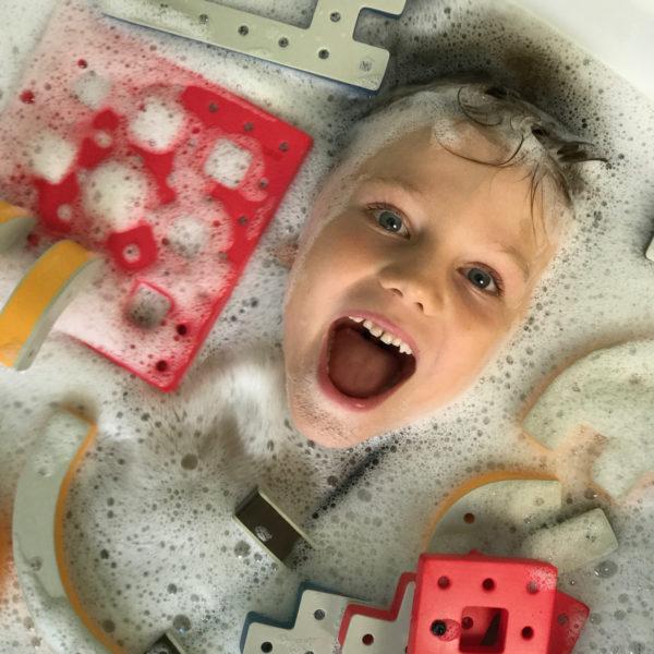 Kind spielt in der Badewanne mit Bakoba Bausteinen
