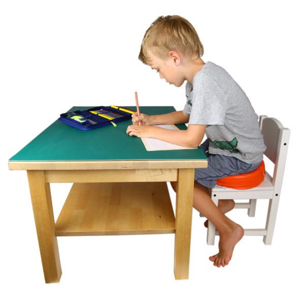 Kind arbeitet konzentriert auf dem Vibrationskissen sitzend