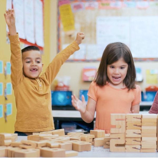 Kinder freuen sich über erfolgreiche Selbstkontrolle ihres Rechenergebnisses mit den Sumblox Summenbausteinen für Kindergarten und Schule