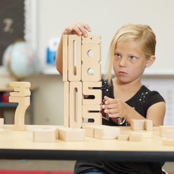 Kind arbeitet konzentriert mit den Sumblox Summenbausteinen für Kindergarten und Schule