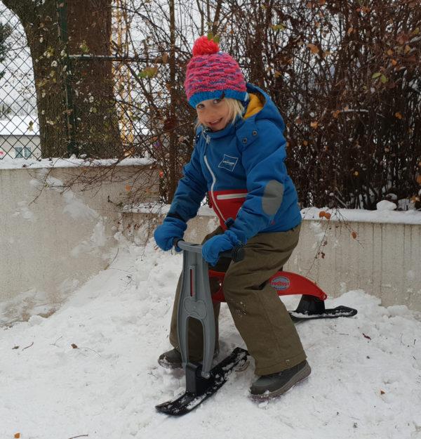 Kindergartenkind fährt mit dem Skibob mini im Garten