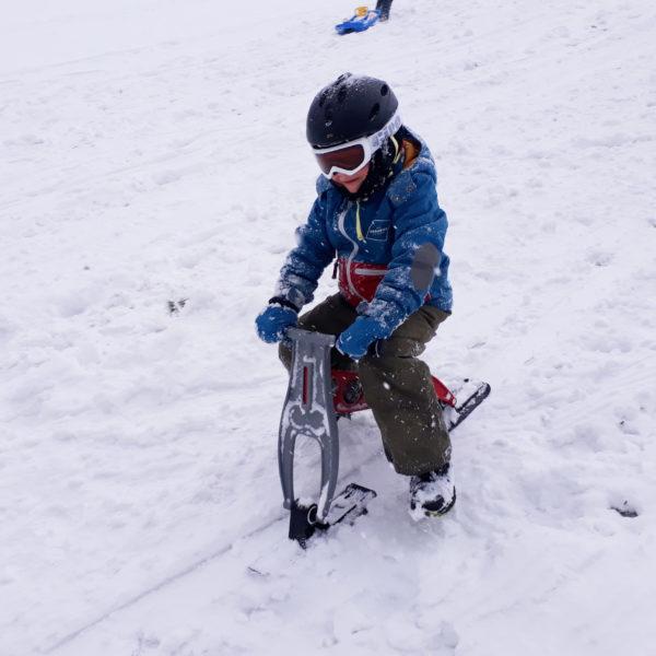 Kindergartenkind fährt mit dem Skibob mini auf der Rodelpiste