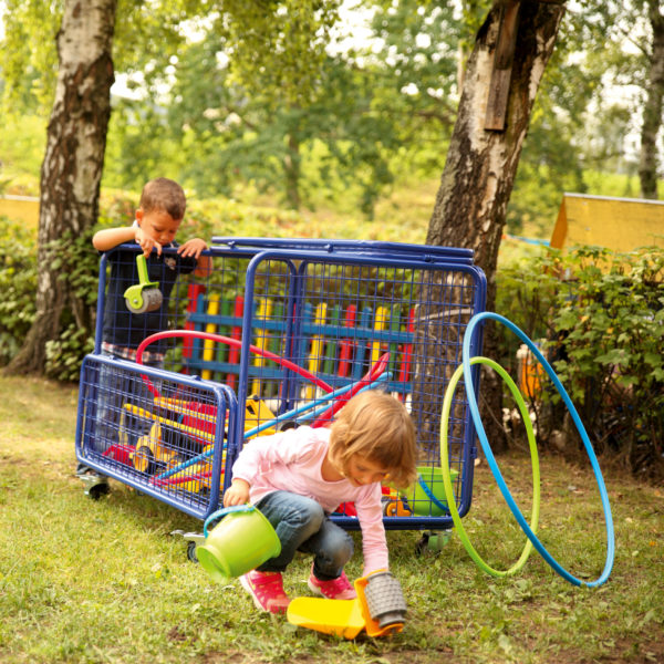Kinder räumen Spielmaterial in Transportwagen