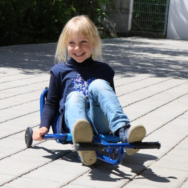 Foto: Kind fährt mit Swing Racer Gartenfahrzeug für Kindergarten-Kinder