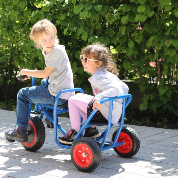 Foto: Kinder fahren mit Sitzbank-Taxi-Dreirad, einem Gartenfahrzeug für Kindergarten-Kinder