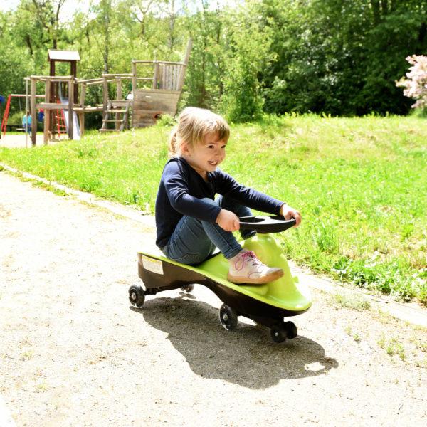 Kindergartenkind fährt auf magic driving car von beleduc durch den Garten