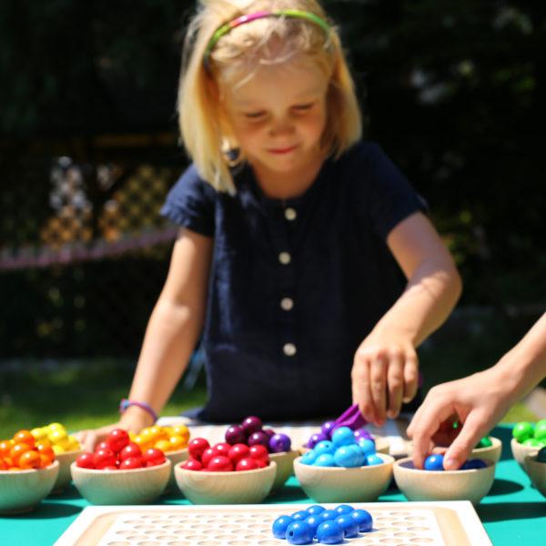 Kindergartenkind sortiert bunte Holzperlen in Materialschälchen aus Holz
