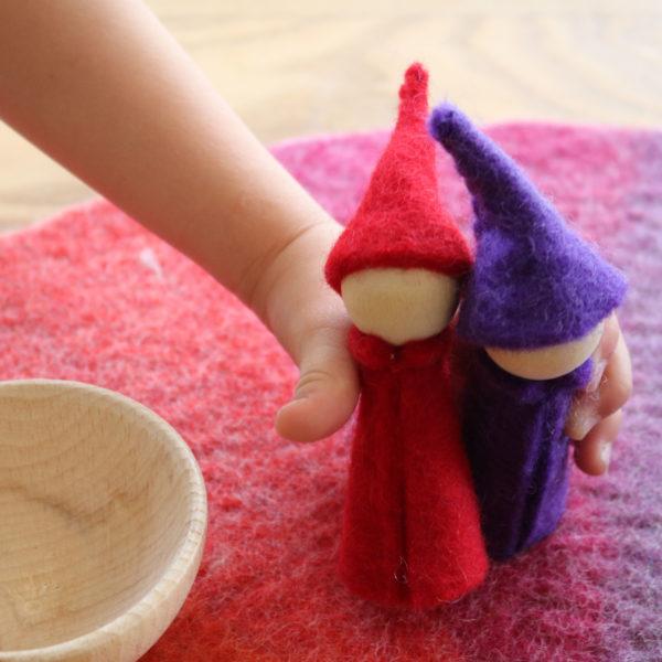 Kinderhand hält Zwerge aus Holz und Filz