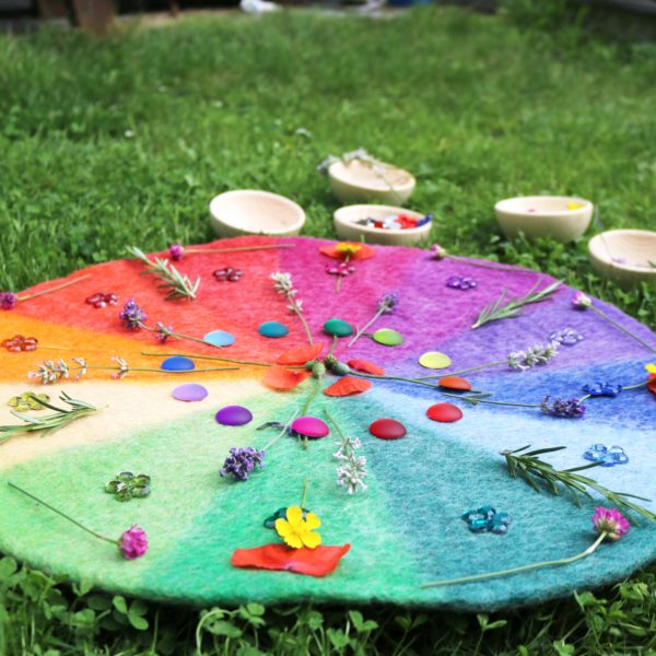 Ein Mandala aus Blumen und Funkelsteinen auf dem Farbenkreis aus Filz
