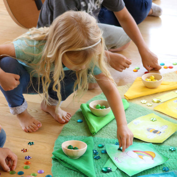 Kind beim Zuordnen von Funkelsteine zu den Farben des Farbenkreises.