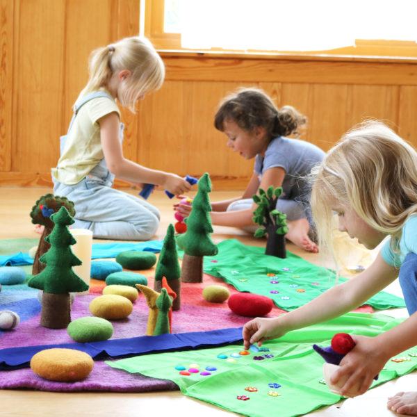Kinder beim Rollenspiel mit dem Farbenkreis und anderen Filzmaterialien.