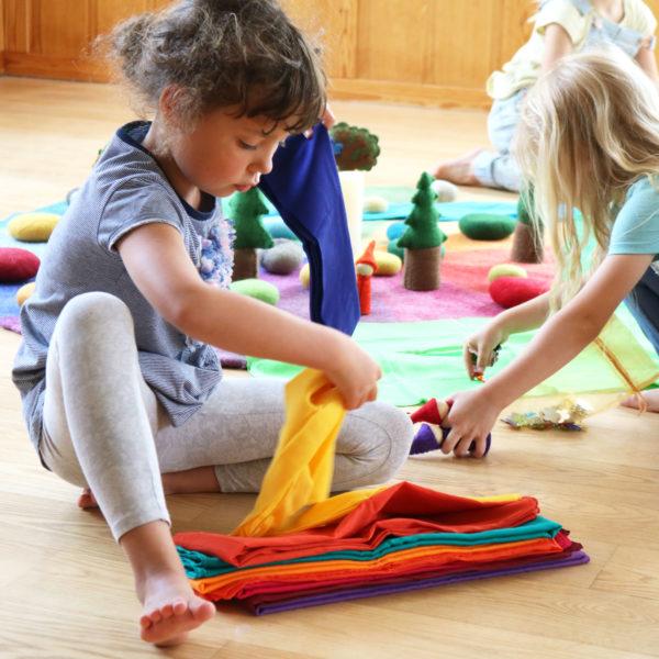 Kindergarten-Kind spielt mit Spieltüchern aus Baumwolle