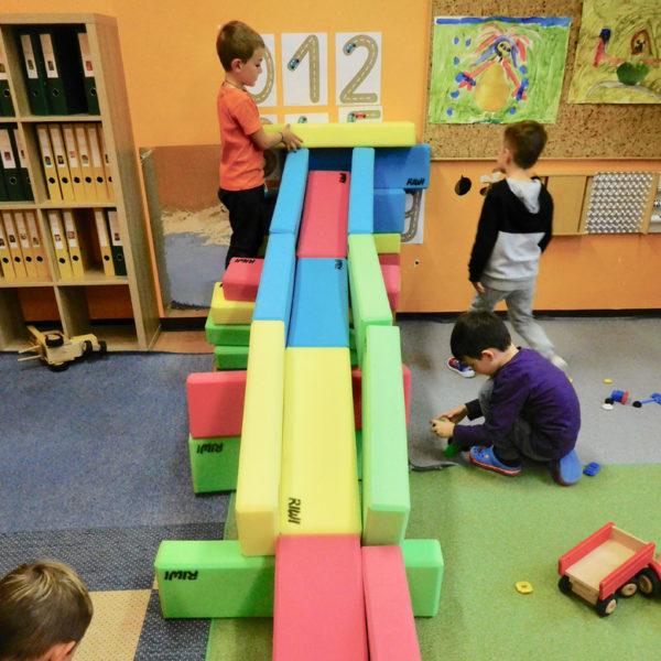 Kindergartenkinder spielen mit einer Kugelbahn aus RIWI Riesen-Softbausteinen