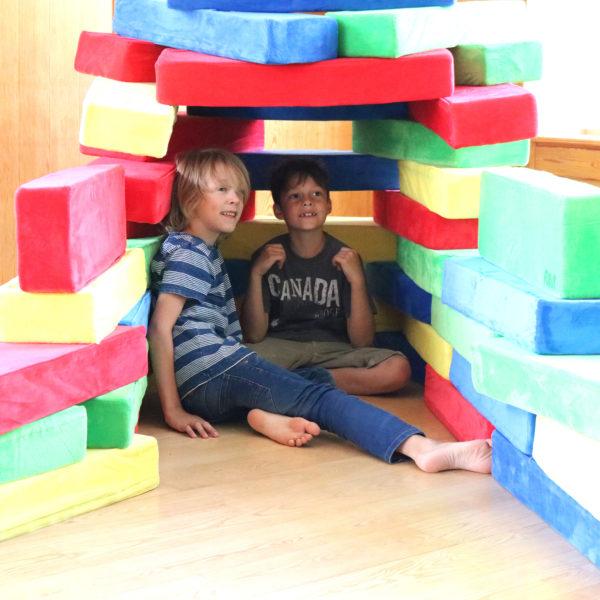 Kinder spielen in einer Höhle gebaut aus RIWI Riesen-Softbausteinen