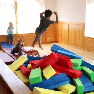 Kindergartenkinder springen im Turnsaal in eine Schitzelgrube aus RIWI Riesen-Softbausteinen