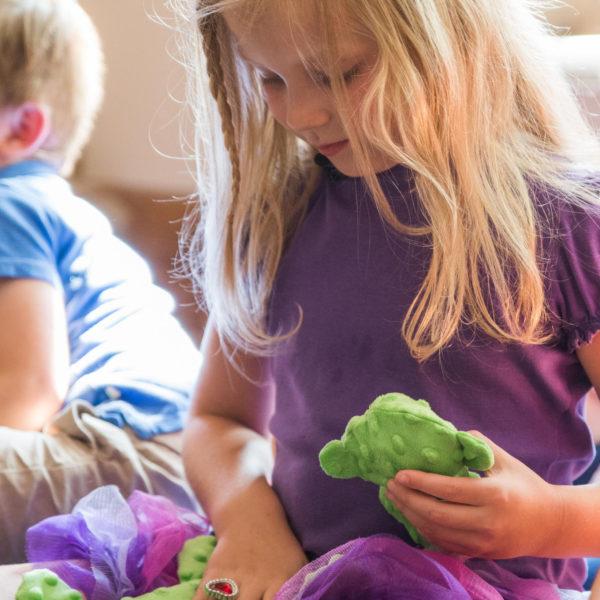 Kind hält Senseez Vibrationskissen mini Schildkröte: Vibationsgeber mit Stoffüberzug.
