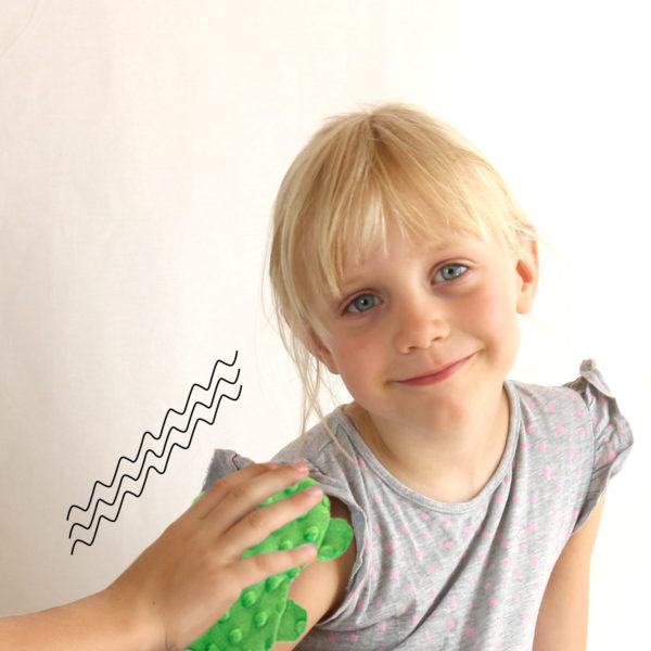Kind entspannt sich mit Senseez Vibrationskissen mini Schildkröte: Vibationsgeber mit Stoffüberzug.