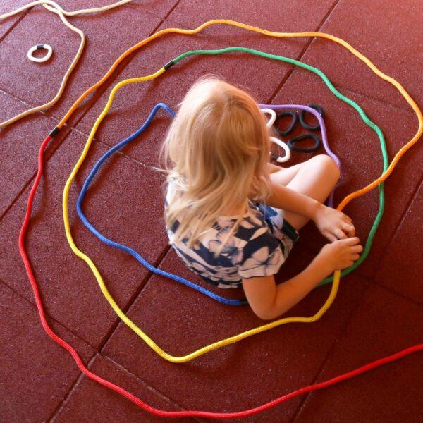 Kind steckt Regenbogenseile zusammen und legt sie auf