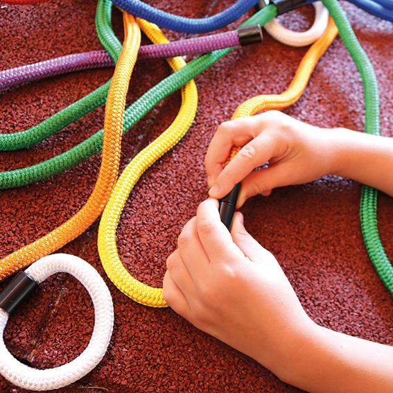 Kinderhände fügen die magnetischen Seilenden der bunten olifu Regenbogenseile zusammen
