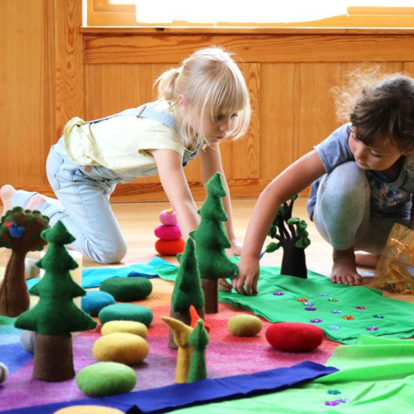 Kinder spielen mit Spielzeug aus Filz und Holz im Kindergarten