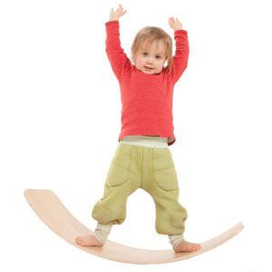 Kind balanciert auf dem Brett aus Holz