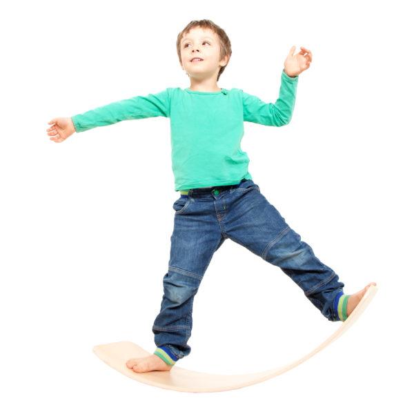 Kind turnt auf dem Balance-Brett aus Holz