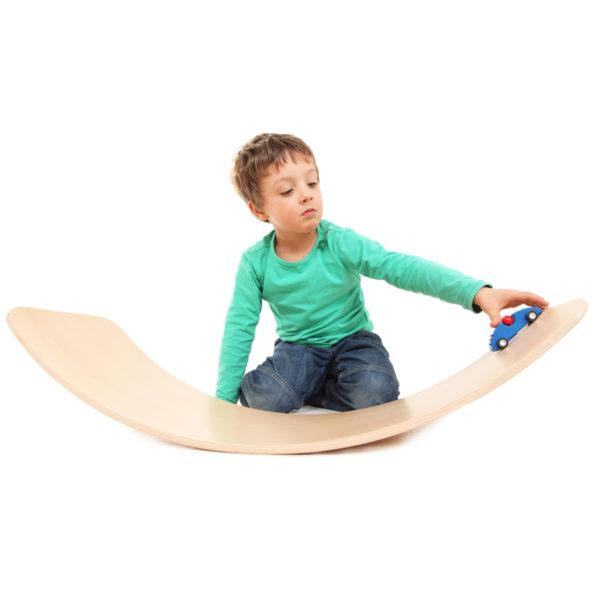Kind spielt mit Auto auf dem Brett aus Holz