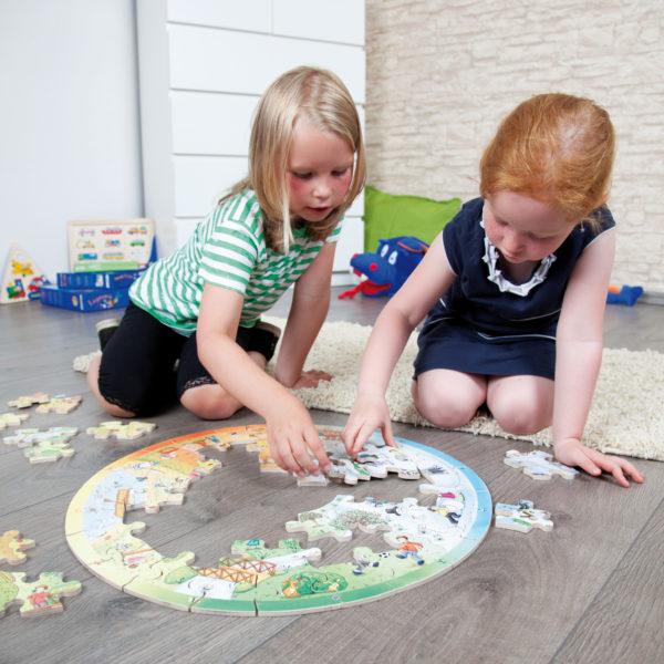 2 Kinder im Kindergartenalter sitzen am Boden um das runde XXL Lernpuzzle von beleduc