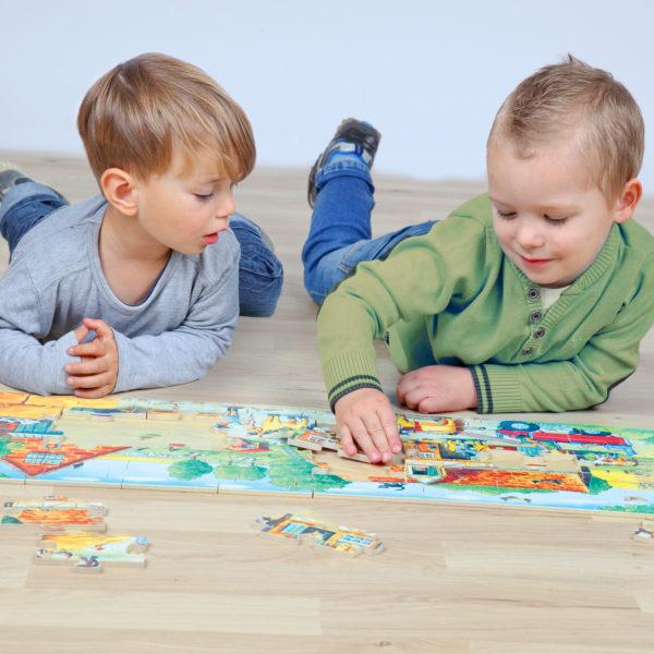 2 Kinder im Kindergartenalter liegen am Boden und haben Spaß beim Zusammensetzen des Puzzles Pony Farm