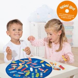 Kinder im Kindergartenalter spielen an einem Tisch mit dem Würfelspiel Candy. Zusätzlich abgebildet ist das Spiel Gut Logo