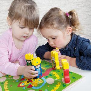 Zwei Kinder im Krippenalter spielen mit dem kurzweiligen Brettspiel Castelino