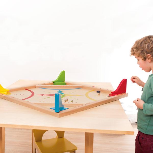 Kind lässt Metallkugel über eine Holzrutsche auf das Spielbrett rollen